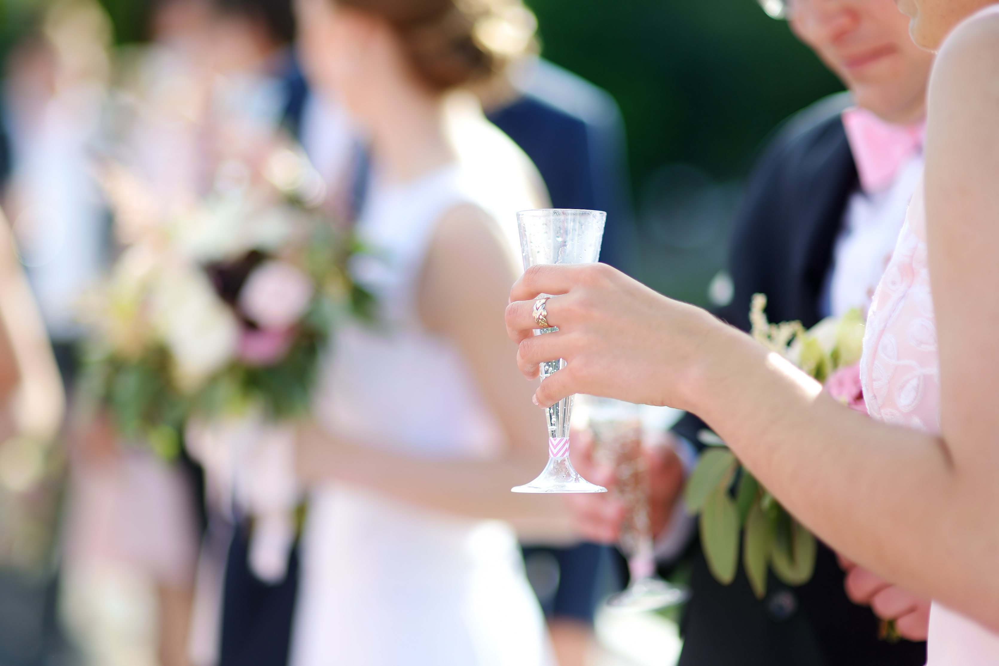 Woman holding a glass of champagne at some festive event, party or wedding reception